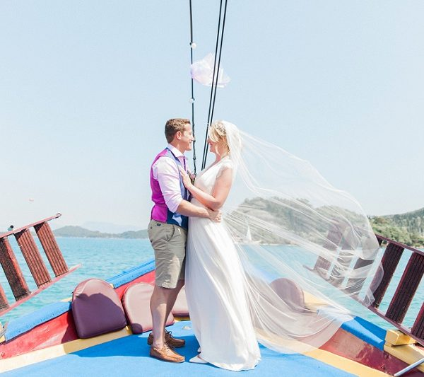 Bride wearing Laverne wedding dress by Catherine Deane and groom on a boat in Nidri | Maxeen Kim Photography