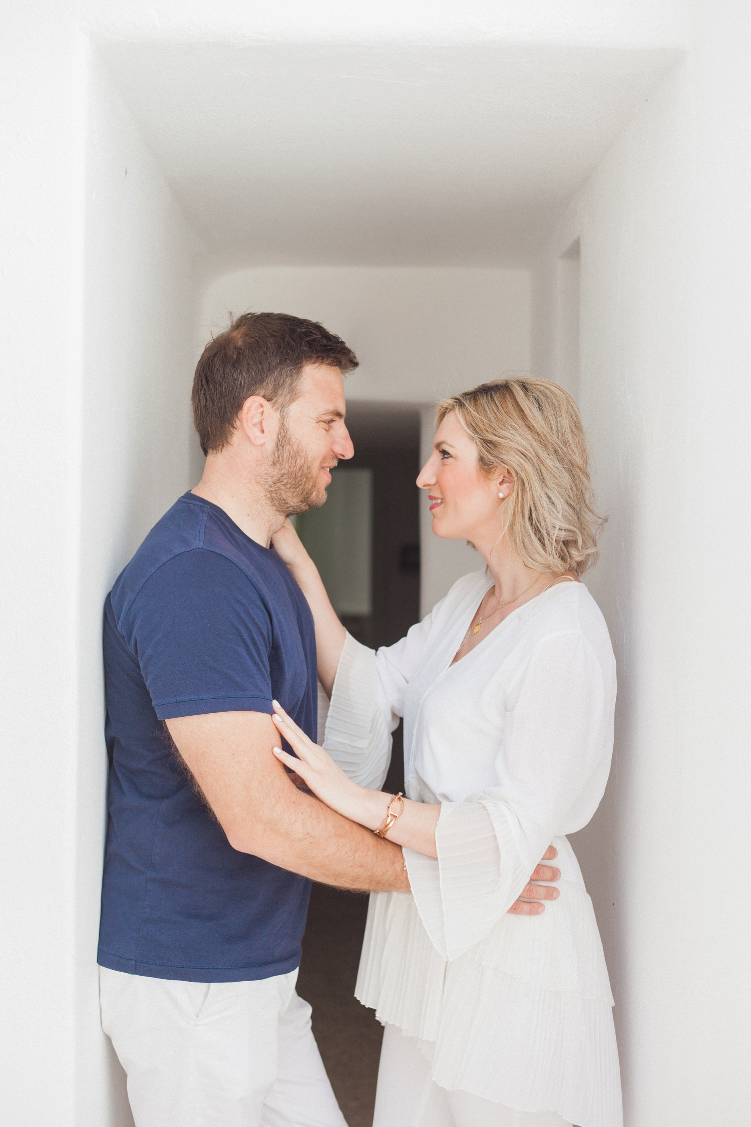 Couple smile at each other in a whitewashed corridor during their shoot at Artemoulas Studios Mykonos