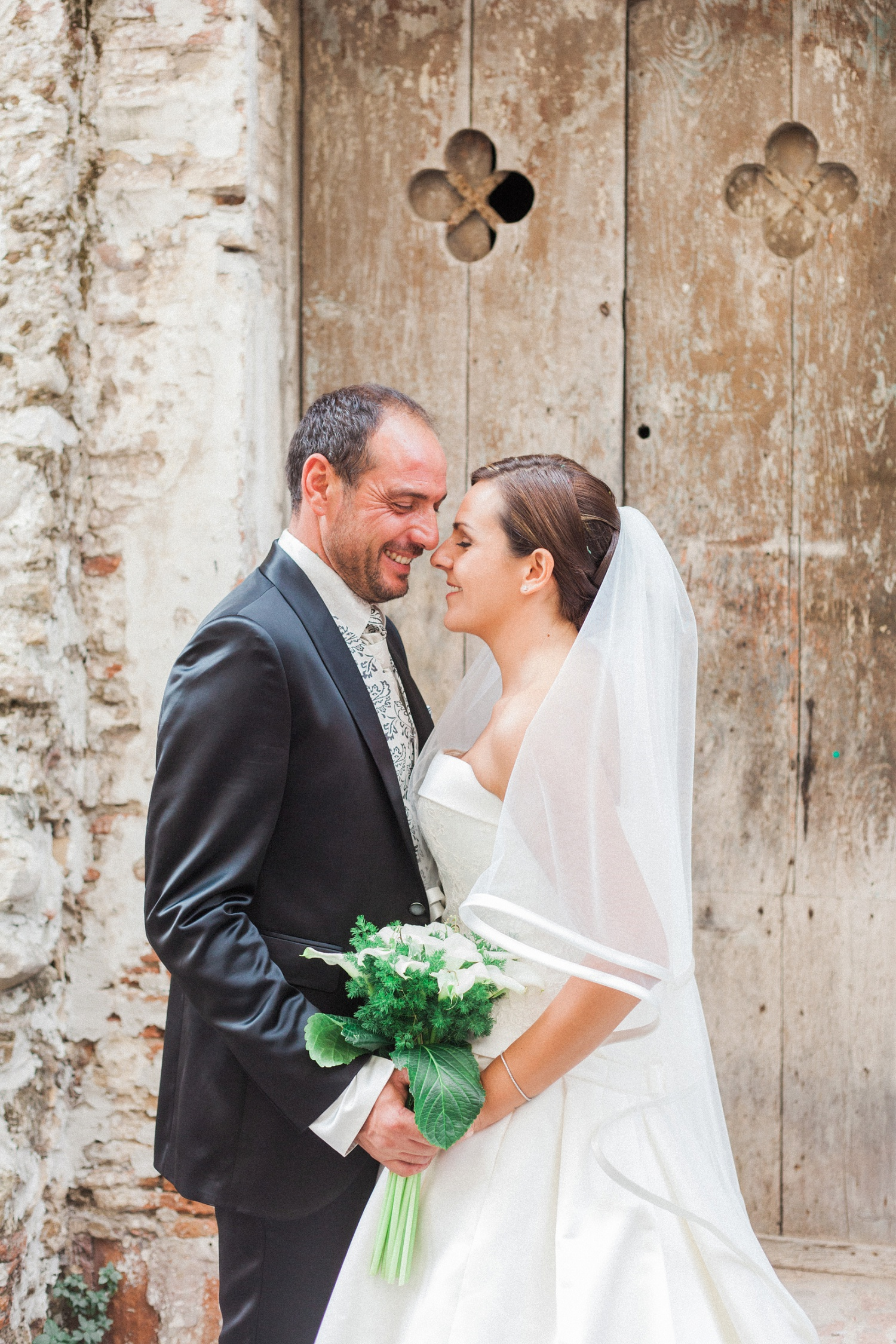 Italian bride and groom stand together in front of a beautiful old door during their wedding at the Convivium Hotel in Vasto Abruzzo
