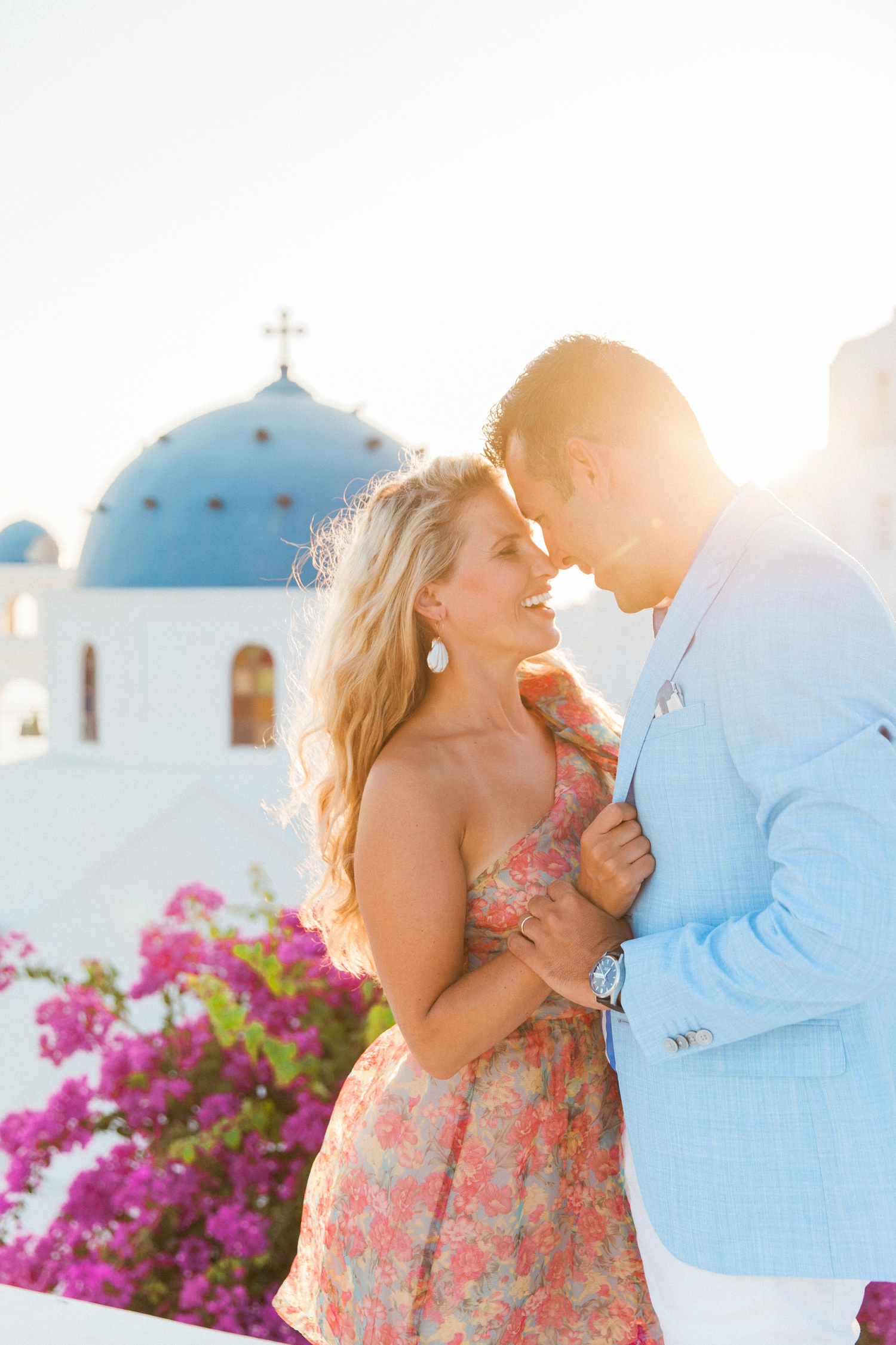 Sunset portraits of a couple in front of a church during their Santorini honeymoon photography session